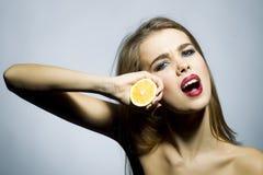 Junges blondes Mädchenporträt mit Orange Stockfoto
