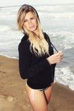 Junges blondes Mädchen in Meer in Badeanzug und im Sweatshirt mit Haube Stockfotografie