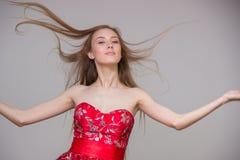 Junges blondes Modell mit dem langen Haar in einem intelligenten roten Kleid, das Spaß auf einem grauen Hintergrund im Studio läc Lizenzfreies Stockfoto