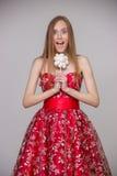 Junges blondes Modell mit dem langen Haar im roten Kleid mit Süßigkeit in den Händen, die Spaß auf grauem Hintergrund im Studio l Lizenzfreies Stockfoto