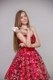 Junges blondes Modell mit dem langen Haar im roten Kleid mit Süßigkeit in den Händen, die Spaß auf grauem Hintergrund im Studio l Stockfoto
