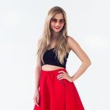 Junges blondes Modell Sonnenbrille, das des neuen modernen Sommerblick-, -c$tragenkreises, roter Rock und schwarze ärmellose Spit Lizenzfreie Stockfotos