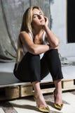 Junges blondes schönes Mädchen sitzen auf hohen Absätzen Lizenzfreies Stockbild