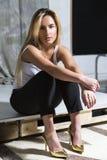 Junges blondes schönes Mädchen sitzen auf hohen Absätzen Lizenzfreie Stockfotos