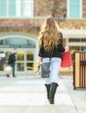 Junges blondes weibliches Einkaufen mit den rosa und roten Taschen, die einen Handy halten Lizenzfreies Stockfoto