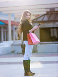 Junges blondes weibliches Einkaufen mit den rosa und roten Taschen, die einen Handy halten Lizenzfreie Stockfotos
