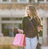 Junges blondes weibliches Einkaufen mit den rosa und roten Taschen, die einen Handy halten Stockfotos