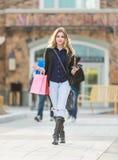 Junges blondes weibliches Einkaufen mit den rosa und roten Taschen, die einen Handy halten Lizenzfreie Stockbilder
