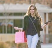 Junges blondes weibliches Einkaufen mit den rosa und roten Taschen, die einen Handy halten Stockfotografie