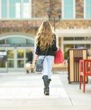 Junges blondes weibliches Einkaufen mit den rosa und roten Taschen, die einen Handy halten Lizenzfreies Stockbild