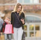 Junges blondes weibliches Einkaufen mit den rosa und roten Taschen, die einen Handy halten Stockfoto