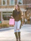 Junges blondes weibliches Einkaufen mit den rosa und roten Taschen, die einen Handy halten Stockbild
