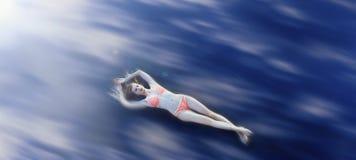 Junges blondes weibliches Lügen auf Wolken Tag, im Freien Stockfotografie