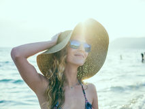 Junges blondy Mädchen in der Sonnenbrille und im Strohhut am Strand Stockfotos