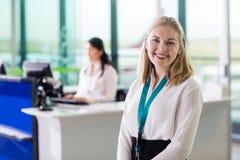 Junges Bodenpersonal, das während Kollege arbeitet am Flughafen bezüglich lächelt lizenzfreies stockbild