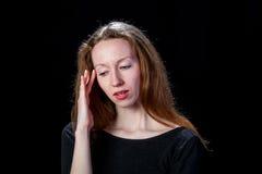 Junges braunes Haarmädchen mit Kopfschmerzen auf schwarzem Hintergrund Stockfoto