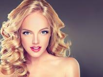 Junges breites lächelndes blondes behaartes Mädchenmodell Stockfoto