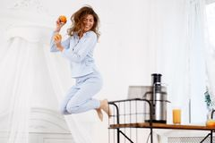Junges brunette Mädchen gekleidet in den hellblauen Pyjamasprüngen mit Orangen in ihren Händen im hellen Raum nahe bei lizenzfreie stockfotos