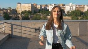 Junges brunette Mädchen mit langem Haartanzen in der Stadt auf einem Sonnenunterganghintergrund stock video