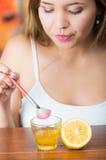 Junges Brunettefrauensitzen, beim Eintauchen Bürste in Glas goldenen Honig bilden Sie, geschnittene Zitrone auf der Seite Lizenzfreie Stockfotos