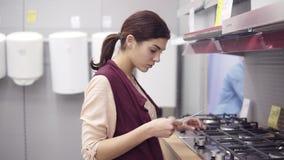 Junges Brunettemädchen bedrängt Brennerknöpfe auf cooktop des Küchenofens und nimmt den Preis von der Anzeige in der Hardware stock footage