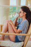 Junges Brunettemädchen, das auf dem Balkon und dem trinkenden Kaffee sitzt Stockfoto