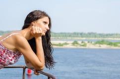 Junges Brunettemädchen, das durchdacht Abstand auf dem Hintergrund des Flusses untersucht Lizenzfreie Stockfotografie