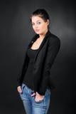 Junges Brunettemädchen in der Mantelhaltung Lizenzfreies Stockfoto