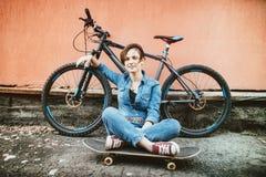 Junges Brunettemädchen mit dem kurzen Haar, das nahes Weinlesefahrrad steht und ein Skateboard, Spaß und eine gute Laune habend w lizenzfreie stockfotografie