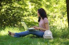 Junges Brunettemädchen mit Laptop draußen arbeitet Lizenzfreie Stockfotografie