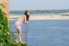 Junges Brunettemädchen steht auf Balkon vom alten gegen den Hintergrund des Flusses und untersucht durchdacht das dist Stockfoto
