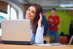 Junges busineswoman, das im Büro mit Laptop sitzt Lizenzfreie Stockfotos