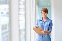 Junges busineswoman, das Klemmbrett im hellen Korridor mit Fenster hält stockfoto