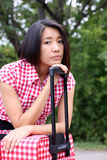 Junges chinesisches Sitzen auf Koffer mit traurigem Gesicht lizenzfreie stockfotos