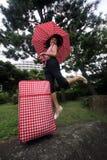 Junges chinesisches Springen mit Regenschirm und Koffer stockfoto