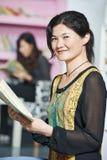 Junges chinesisches Studentenmädchen mit Buch in der Bibliothek Stockfotografie