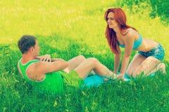 Junges coumple, das auf Gras in Park instagram Zauntritt ausübt Stockfotos