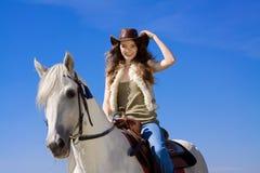 Junges Cowgirl auf Lächeln des weißen Pferds lizenzfreie stockbilder