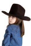 Junges Cowgirl, das über ihrer Schulter mit einem starken Blick schaut Lizenzfreie Stockfotografie