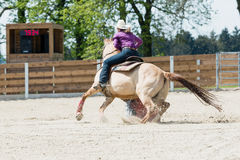 Junges Cowgirl, das ein schönes Farbenpferd in einem laufenden Ereignis des Fasses an einem Rodeo reitet stockfotografie