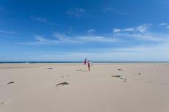 Junges dünnes Mädchen, das auf dem breiten sandigen Strand und der Wellenhand auf dem Hintergrund des blauen Himmels steht Lizenzfreie Stockbilder