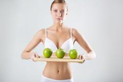 Junges dünnes Mädchen, das einen grünen Apfel hält Stockfoto