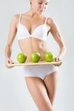 Junges dünnes Mädchen, das einen grünen Apfel hält Lizenzfreies Stockfoto