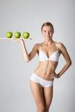 Junges dünnes Mädchen, das einen grünen Apfel hält Lizenzfreies Stockbild