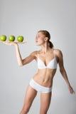 Junges dünnes Mädchen, das einen grünen Apfel hält Stockfotografie