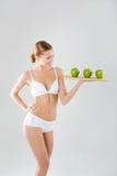 Junges dünnes Mädchen, das einen grünen Apfel hält Stockfotos