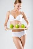 Junges dünnes Mädchen, das einen grünen Apfel hält Stockbilder