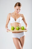 Junges dünnes Mädchen, das einen grünen Apfel hält Lizenzfreie Stockfotografie