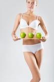 Junges dünnes Mädchen, das einen grünen Apfel hält Stockbild