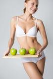 Junges dünnes Mädchen, das einen grünen Apfel hält Lizenzfreie Stockfotos